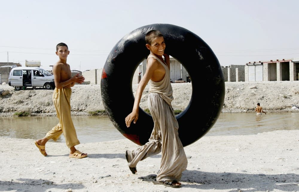 Afghan boy carries a tube for swimming