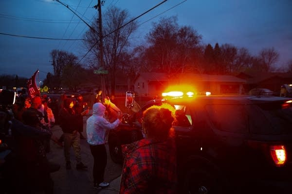 A police car attempts to leave a scene and is blocked by a crowd.