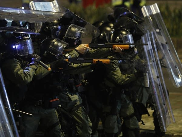 Riot police officers point weapons during a confrontation with protesters