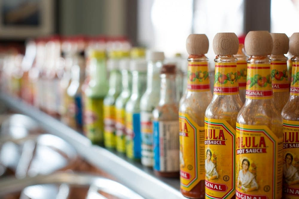 A counter lined with different hot sauces at Sea Salt Eatery.