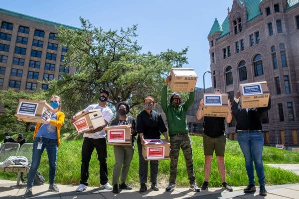 People hold boxes in the air for a photo.