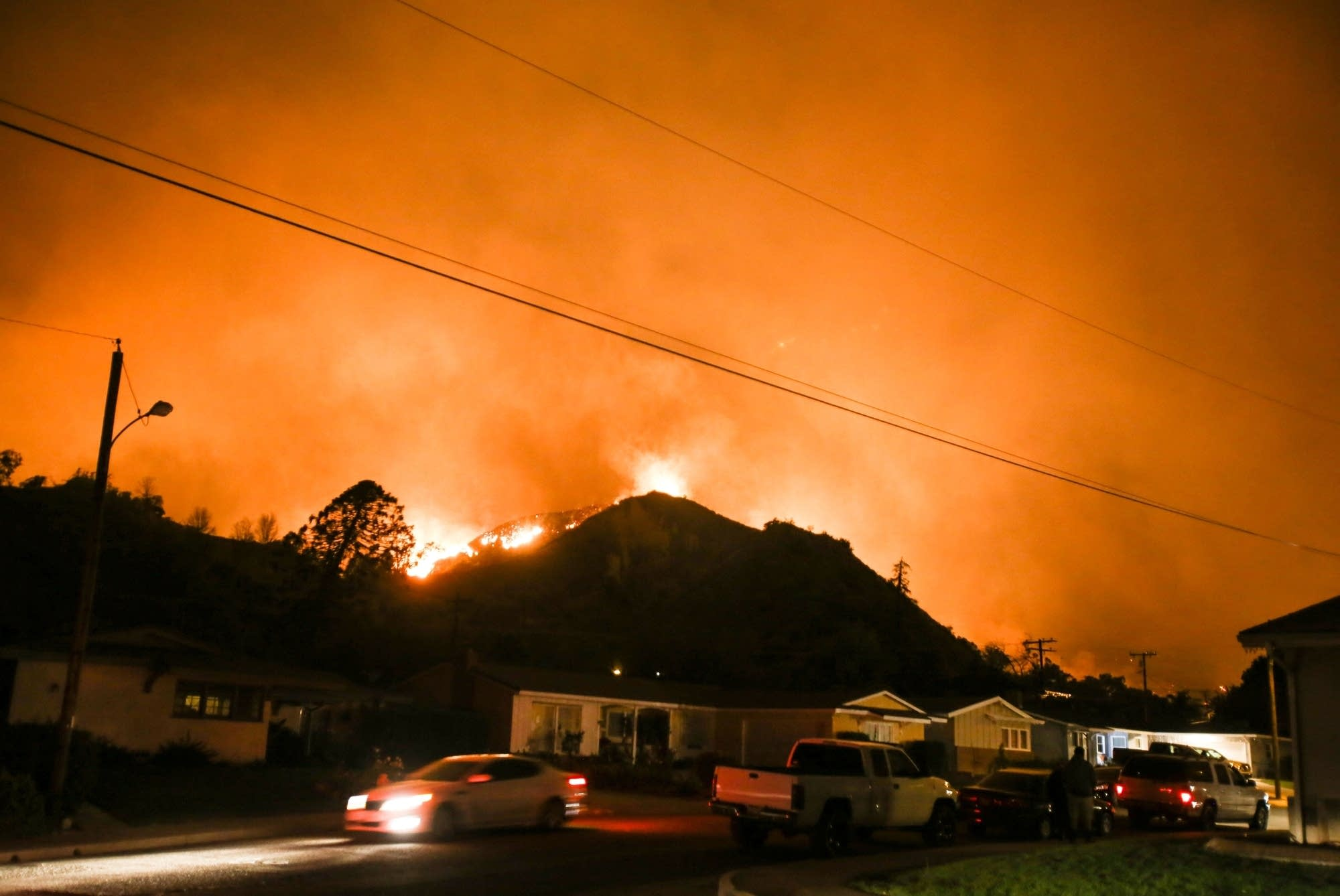 A wildfire burns along a hillside near homes in Santa Paula, Calif.