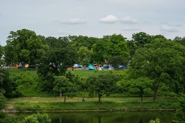 Tents are seen from across a lake.