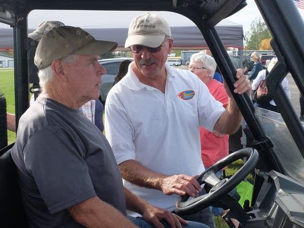 two men talk in an all terrain vehicle