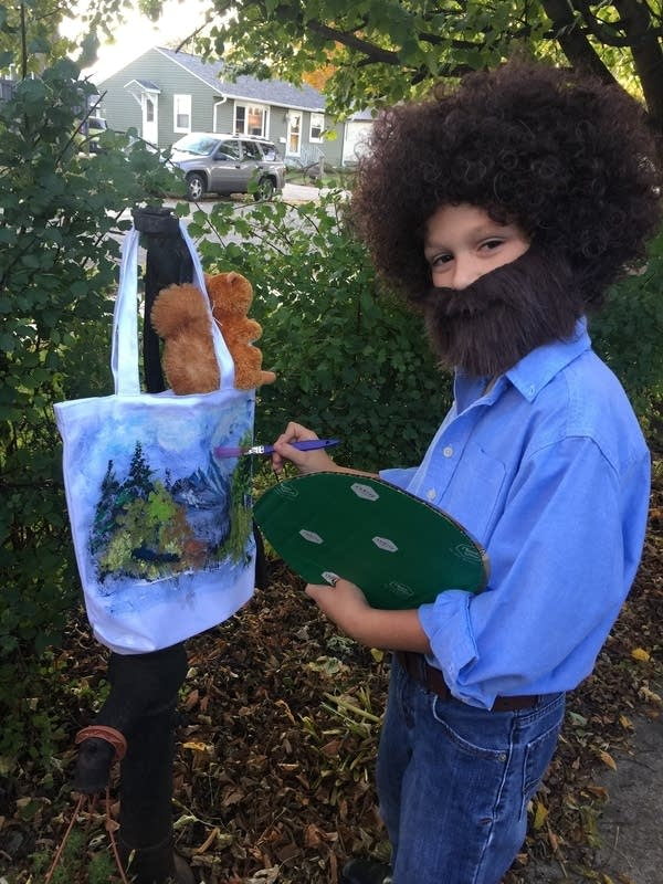 A child dressed in a wig and beard. Holding painting supplies