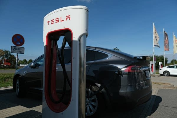 A Tesla electric car charges at a Tesla charging station