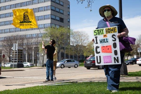 A nurse holds a sign at a sidewalk.
