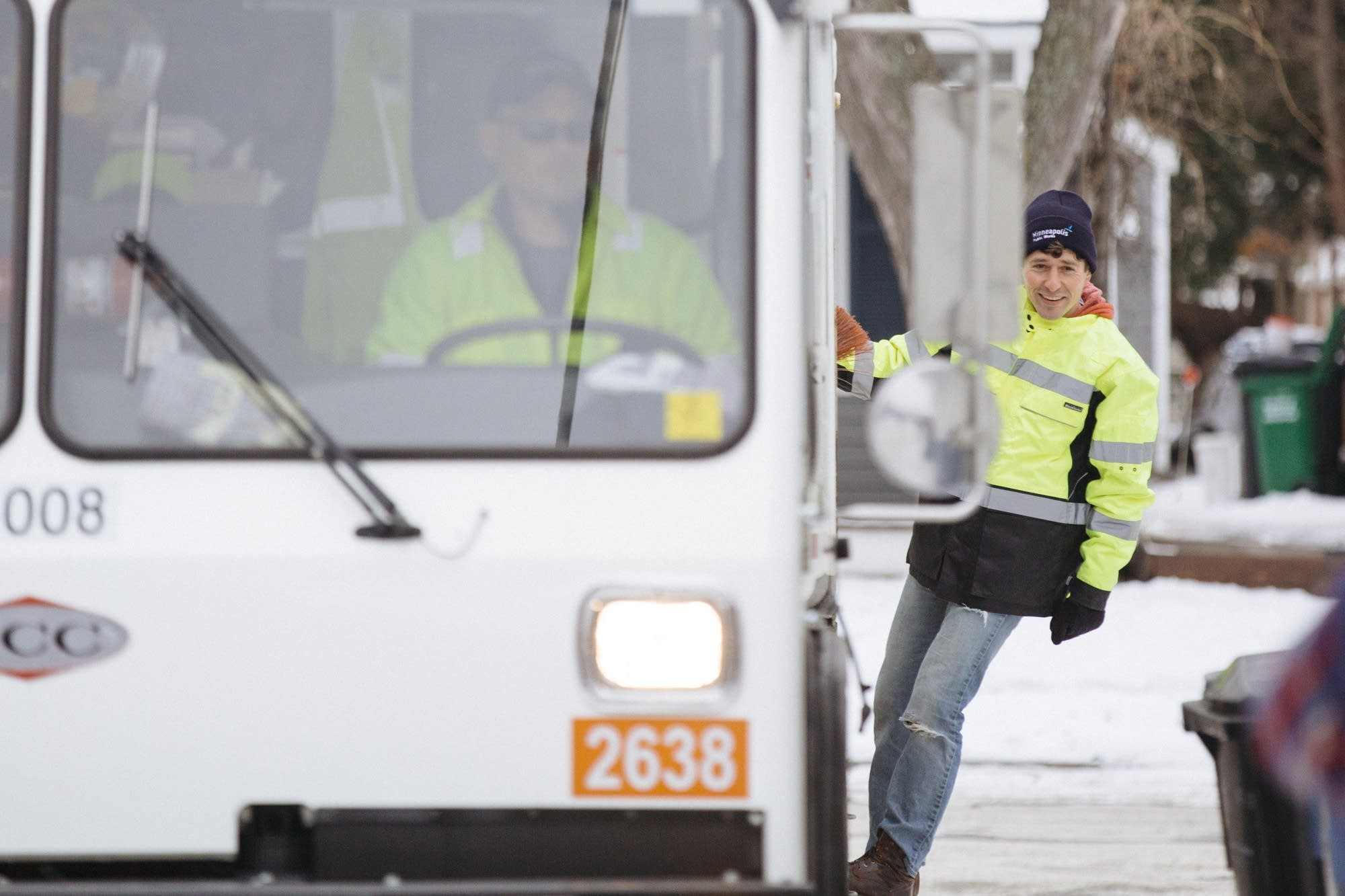 Jacob Frey rides on the back of an organics recycling truck.