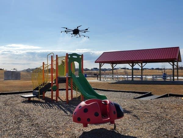 a drone flies near a playground