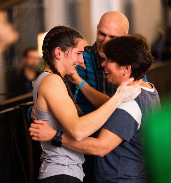 Three people hug.