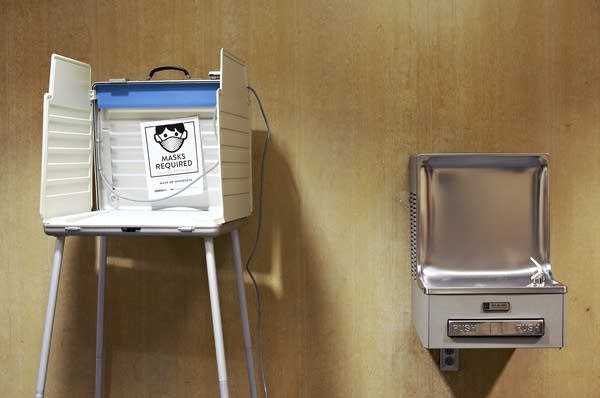 A voting booth with a sign