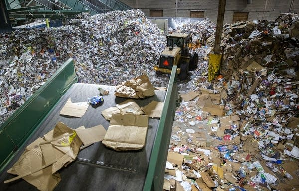 Cardboard and paper on a conveyer belt drops into large piles.