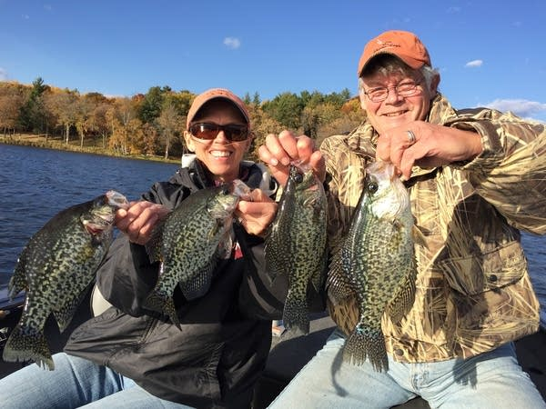 Two people hold up fish they caught at a lake.
