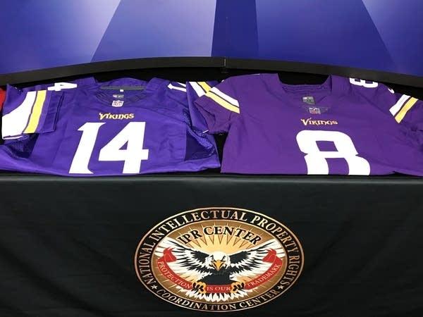 Federal officials display a counterfeit and a real jersey.