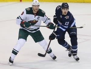 Eric Staal of the Wild (left) and Brandon Tanev of the Jets