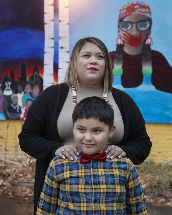 A woman stands with her son in front of a mural.