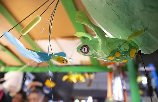 A paper mache frog and dragonfly are hung up to dry.