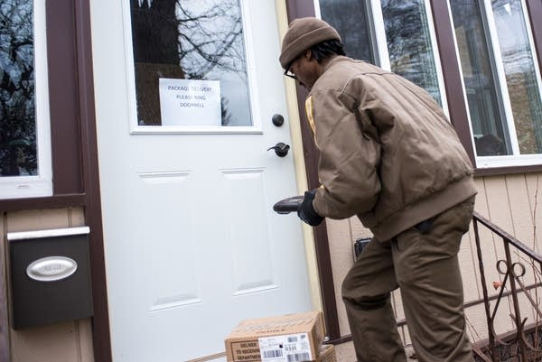 UPS driver Demone Eady drops off a package.
