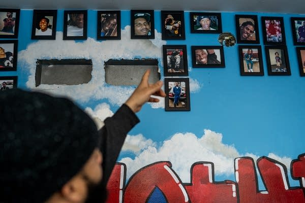 A man points at a wall of photos of men and women who have died.