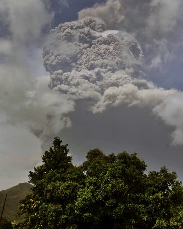 Plumes of ash rise from a volcano