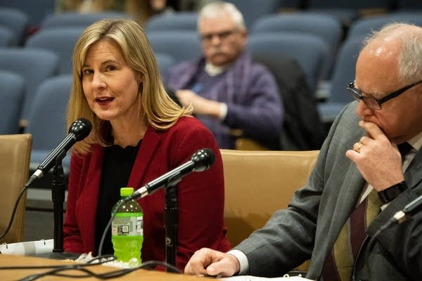 A woman speaks into a microphone next to a man.