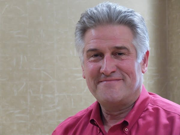 a grey haired man smiles at the camera