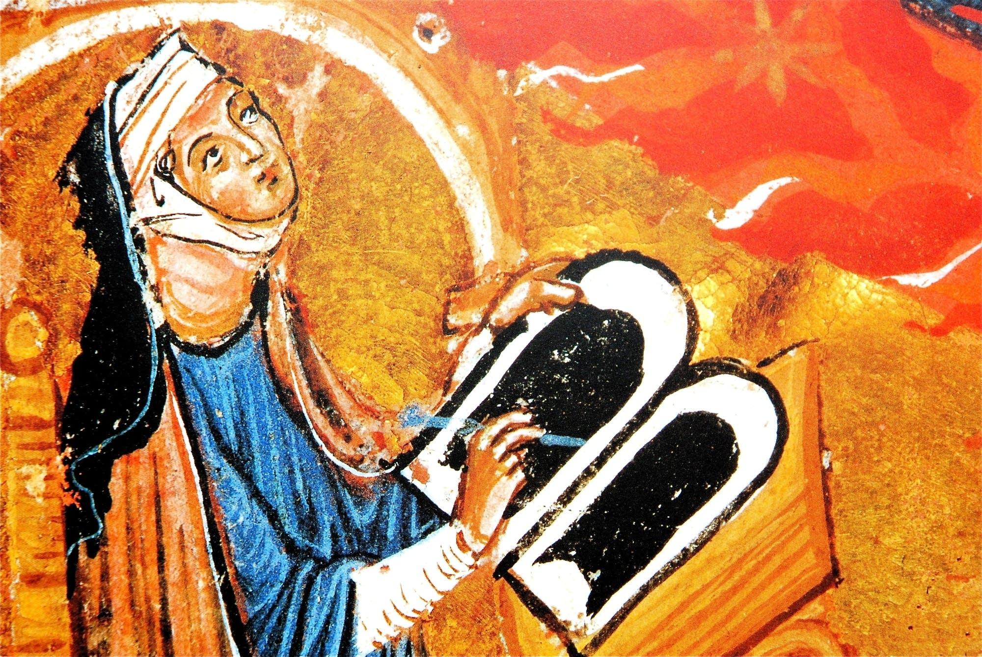 Hildegard von Bingen composing at her desk.