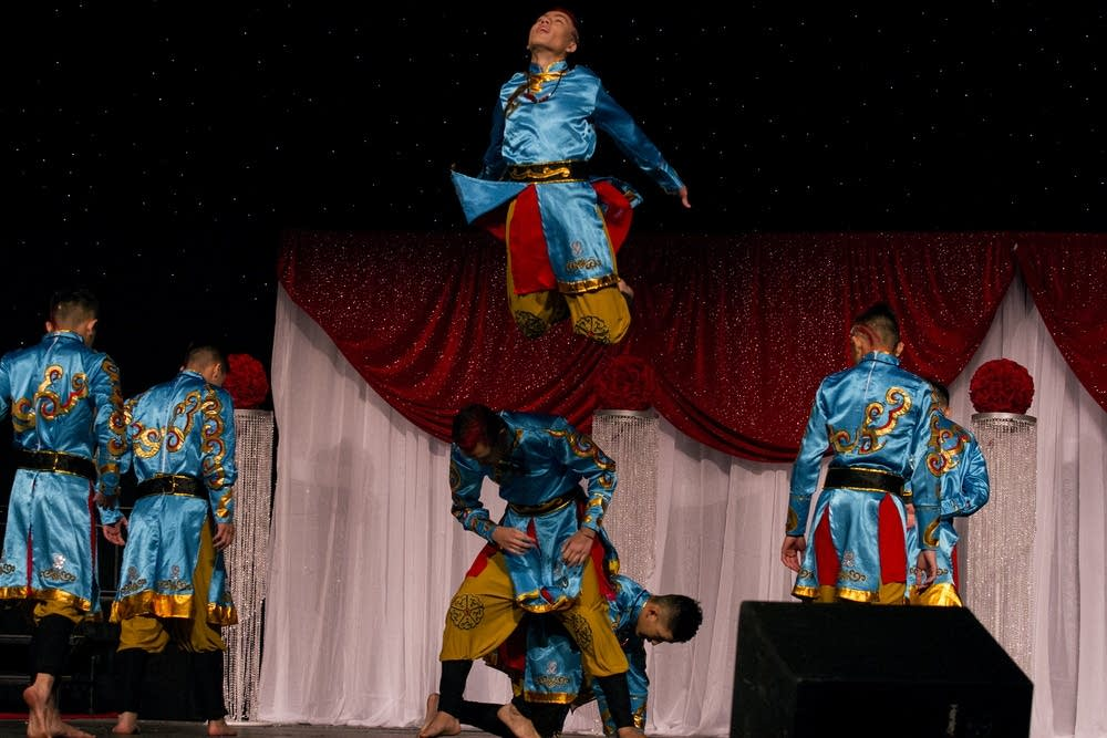 A boys dance group performs on stage.