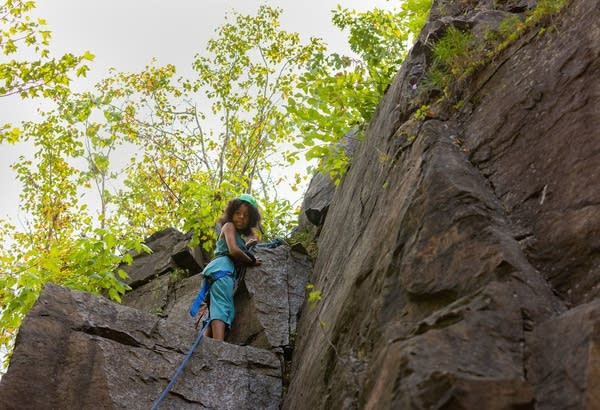 A young girl stands on a ledge while rock climbing.