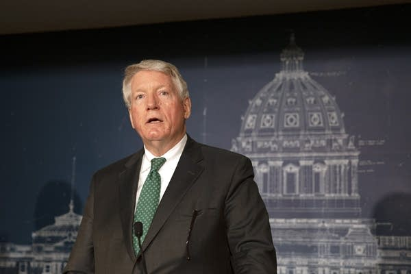 A man in a suit and tie speaks at a podium.