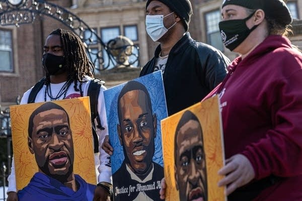 Community activists hold pictures of two men.