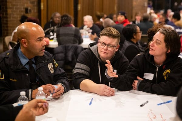 Two women talk to a police officer at a table.