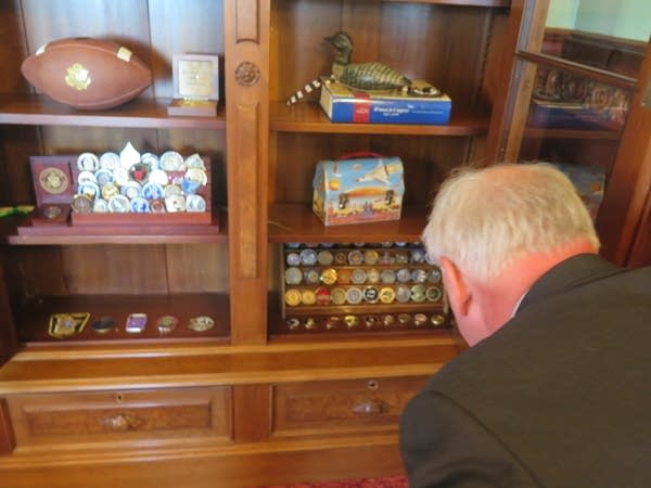 Gov. Tim Walz looks at some of the challenge coins in his collection.