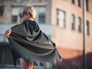 Small boy in a black cape and mask