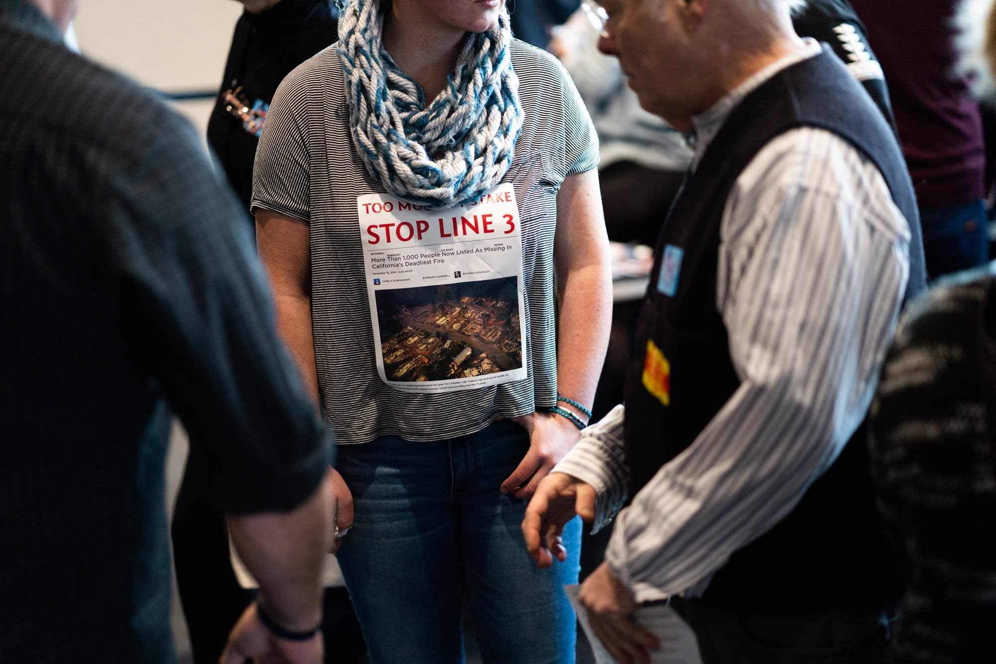 Enbridge Line 3 Oil Pipeline opponents wear printed news articles.