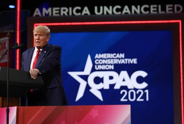 A man stands behind a podium with CPAC on a screen behind him.