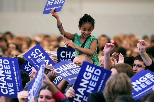 A young supporter holds an Obama sign