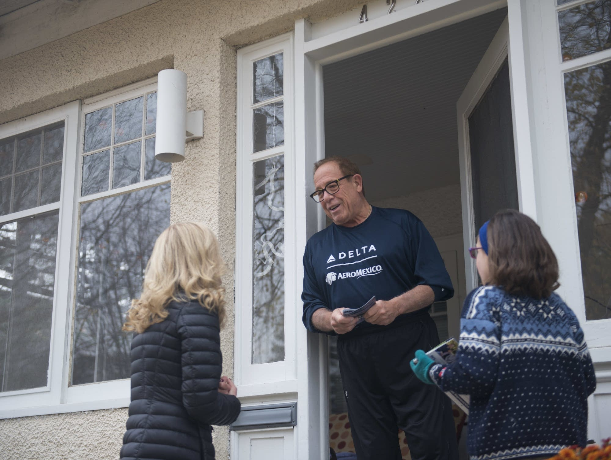 Heather Edelson speaks with election judge Ron Berg at his home in Edina