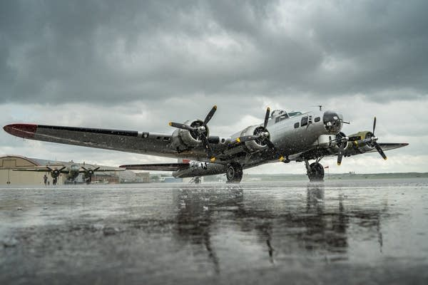 Rain comes down on a B-17G Flying Fortress, front, and a  B-25 Mitchell.
