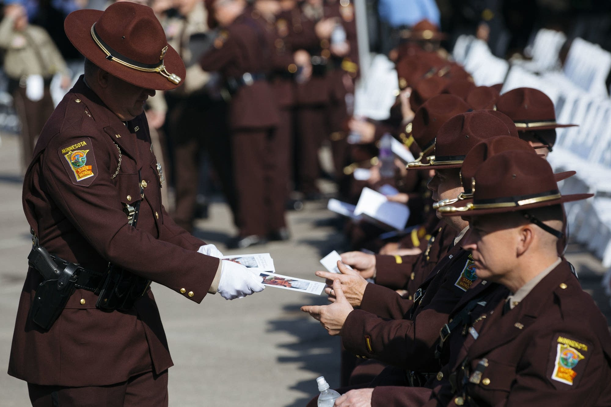 A Minnesota State Patrol officer hands out funeral programs.