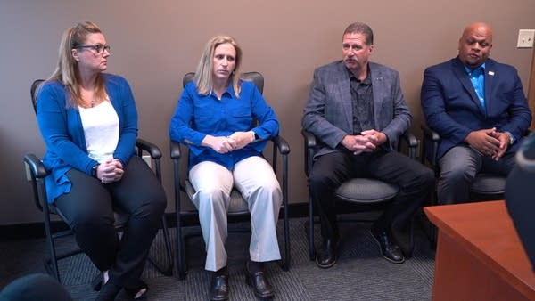 4 people sit in an office