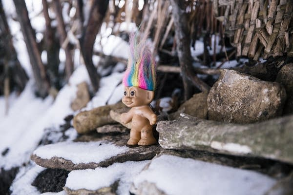 A troll doll stands in one of the stick forts.