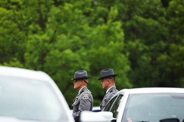 Law enforcement officers walk through the parking lot.