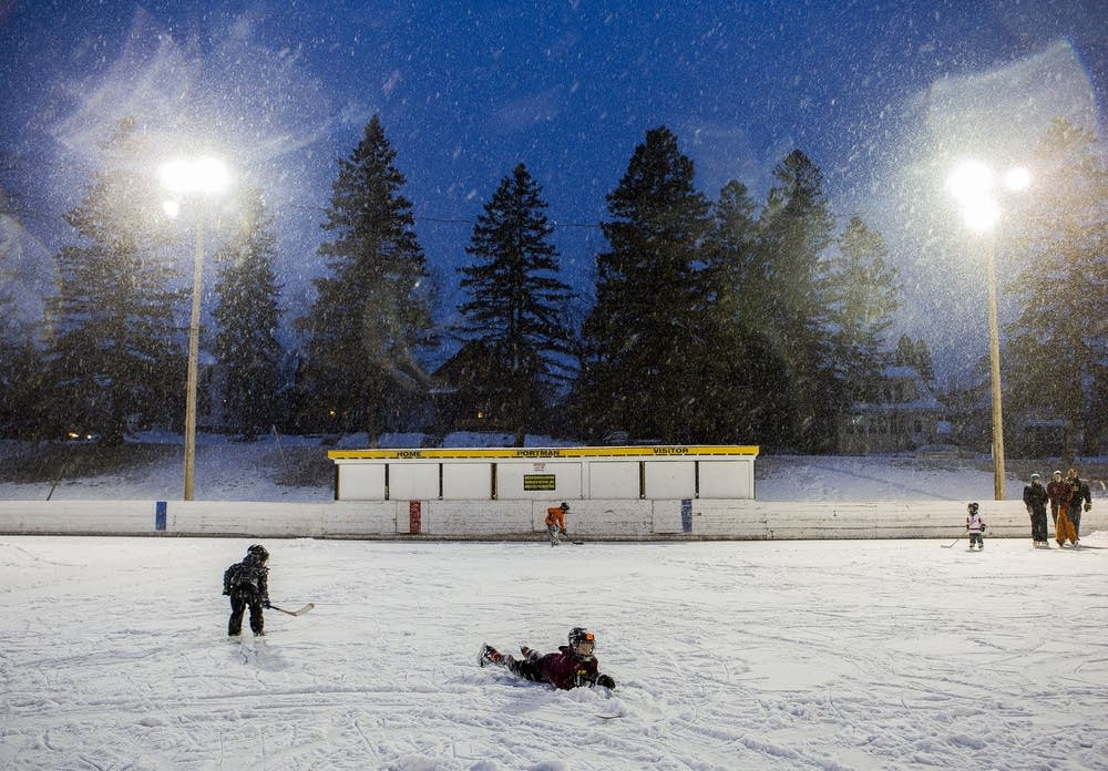 Snow falls and kids slide across the ice.