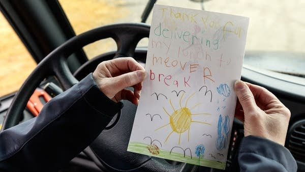 A person holds a note written by a child.
