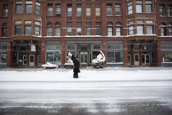 A person walks down a snow-covered road in front of a brick building.
