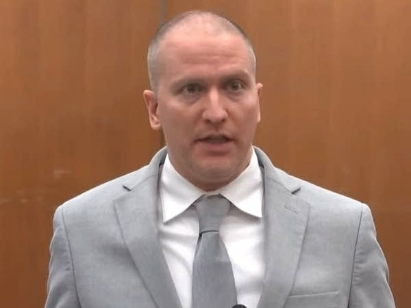 A man stands behind a microphone to speak in a courtroom.