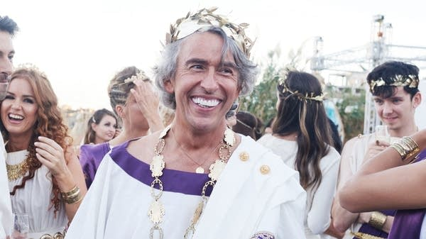 A man smiles, dresses in a Roman toga costume
