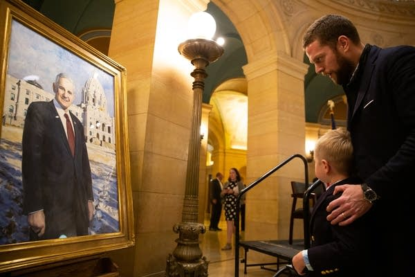 A man holds his son by the shoulders and looks at a painting.