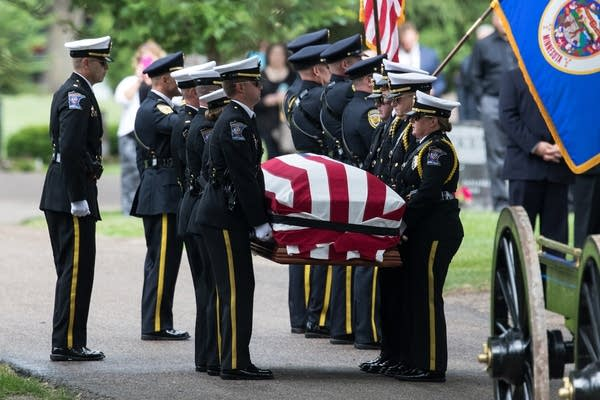 Minnesota law enforcement officers carry the casket of Officer Joseph Gomm.